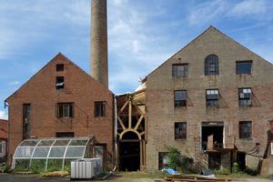Die historischen, aus rotem Ziegel gemauerten Fabrikgebäude erstrecken sich auf eine Länge von 100 m und stehen parallel zueinander