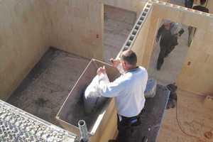 Blähtonschiefer als Dämmstoff wird mithilfe eines Trichters zwischen die Wände gefüllt