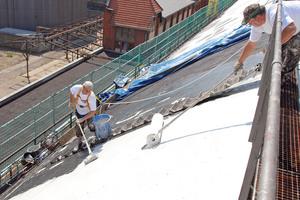 Auf dem stark geneigten Dach einer Maschinenhalle in Berlin-Charlottenburg setzten die Handwerker ein flüssiges Abdichtungssystem ein, das auf senkrechten Flächen haftet
