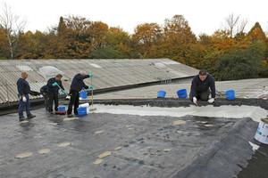 Das 1300 m2 große Dach sollte eine neue Abdichtung erhalten. Für eine ausreichende Haftung reinigten die Verarbeiter den Untergrund und grundierten ihn, bevor sie das Abdichtungssystem auftrugen