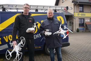 """Dachdeckermeister Thomas Potthast (links) mit der """"DJI Phantom 2 Vision +"""" und Jens Eickmeyer, Inhaber der Dächer von Hunold GmbH, (rechts) mit der """"DJI Phantom 4"""" <span class=""""bildnachweis"""">Foto: Stephan Thomas</span>"""