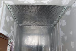 Über dem Vlies wird eine Dampfsperre verlegt und abgeklebt. Danach werden die Wände mit Gipskartonplatten bekleidet