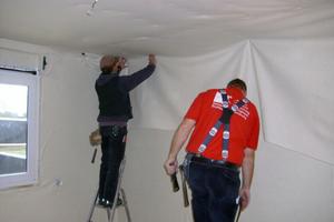 Links: Schadstoffsanierung: Zimmerleute verlegen ein Absorbervlies, das Schadstoffe und unerwünschte Gerüche aufnehmen soll