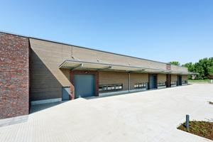 Verwaltungsgebäude mit Klinkersteinen und Lagerhalle mit Holzfassade am neuen Standort eines Fachverlags im Rheinland