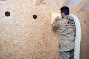 """Auf der Baustelle: Einblasen von Holzfaserdämmstoff mit dem Schlauch <span class=""""bildnachweis"""">Fotos: Gutex</span>"""