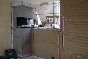 """In der mit Lehmbauplatten beplankten Innenwand liegen die Wandheizungselemente. Darauf wurde ein Lehmstrukturputz aufgetragen<span class=""""bildnachweis""""></span>"""