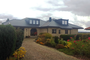 Nach der Sanierung hat der Bungalow zwei neue Dachgauben und ist mit Aluminiumdachschindeln gedeckt