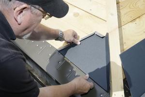 Henry Göppert, Fachverleger von Prefa, zeigte den Handwerkern, wie man die Dachschindeln an schwierigen Stellen verlegt