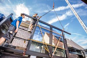 Spanngurte werden am Dachfenster befestigt, um es sicher per Kran auf das Dach zu heben
