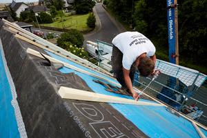 Zur Befestigung schraubten die Handwerker lange Holzbauschrauben schräg durch die Dachlatten und die Dämmung bis in die Sparren hinein