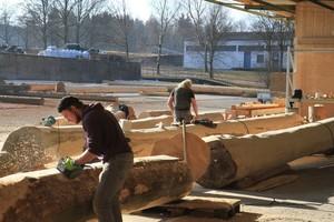 Das Vorbereiten der Naturstämme zum Bau von Blockhäusern ist pure Handarbeit, hier das Abschleifen der entrindeten Stämme<br />