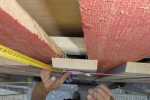Maßarbeit bei der Boden-Deckel-Schalung: Die Schrauben gehen nur durch die Traglatten, nicht durch die roten Bretter