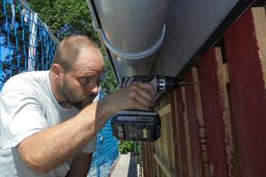 Ralf Tietz verschraubt sägeraue Lärchenholzbretter an der Fassade eines Holzrahmenbaus