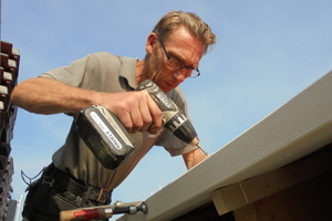 Tischlermeister Martin Exner verschraubt einen Balken am Dachüberstand und vergrößert so die Auflagefläche für die Dachziegel