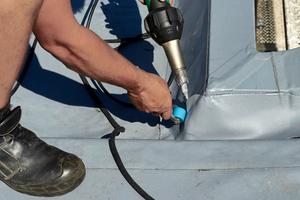 Gefügt wurden die Bahnen mit Heißluft. Hierzu setzten die Dachhandwerker wahlweise einen Schweißautomaten für die Bahnennähte oder Handschweißgeräte (Bild) für die Details ein