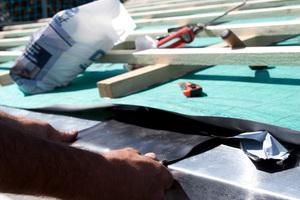 Die Überlappungen der Traufbleche wurden sicher mit einem Streifen Kehlsattelband überklebt ... Foto: Braas