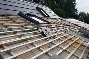 """Kabel, eine Anschlussdose, Haken zum Einhängen – ein umgedrehter Solardachziegel auf einer Dachbaustelle<span class=""""bildnachweis"""">Fotos: SolteQ</span>"""