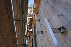 Aluminiumschienen an der Fassade tragen die Unterkonstruktion der Lärchenholzschalung