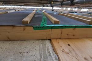 Beton trifft Brettsperrholz: Links eine Betonaußenwand im Erdgeschoss, rechts eine Brettsperrholzwand. Darüber der Fassadenaufbau mit Dämmschicht<br />