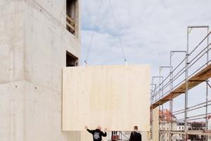 """Um das Treppenhaus aus Beton stellen die Zimmerer die Brettsperrholzwände auf <span class=""""bildnachweis"""">Foto: Peter Eichler, Leipzig</span>"""