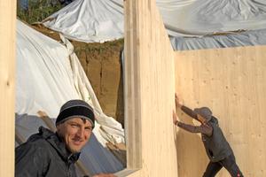Mitte: Bauen macht Freude: Durch das Fensterelement schaut Flaviu Codirla, im Hintergrund arbeitet der Chef