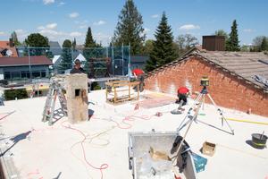 Die oberste Geschossdecke wird für die Aufstockung vorbereitet: Zimmerer verschrauben Winkel für die Massivholzwände