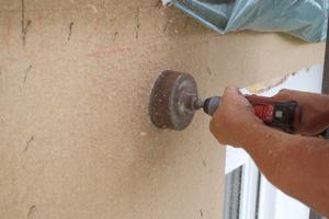 Bohren eines Loches in die Holzfaserplatten zum Einfüllen der Holzfaser-Einblasdämmung