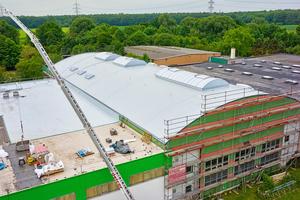 """Die Fabrik mit dem Tonnengewölbedach in der Mitte während der Dacharbeiten<span class=""""bildnachweis"""">Fotos: Alwitra / Sven-Erik Tornow</span>"""