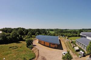 Von der halbrunden zur langen Seite ist das Dach geneigt, rechts am Dachrand sitzt eine Entwässerungsrinne