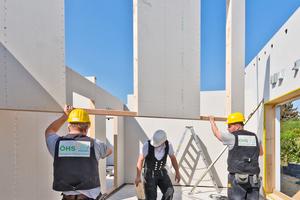 Zimmerer der Firma Ökologischer Holzbau Sellstedt bei der Montage einer mit Gipsfaserplatten beplankten Wand