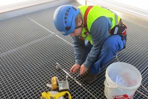 Gesichert am Dachrand: Über einem der Anschlagpunkte verlegen Dachhandwerker einen Gitterrost