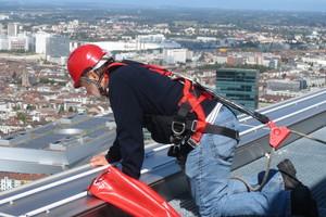 Rolf Hofer, Inhaber und Geschäftsführer der Hofer Dachsicherheit GmbH, bei der Inspektion des Seilsicherungssystems