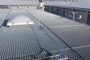Fassadenelemente auf dem Dach bilden eine Brüstung, hinter der sich ein Kran verbirgt