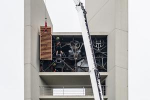 Der Kran mit über 50m Ausladung bringt die neuen Schallläden, die Zimmerer nehmen sie am Glockenstuhl entgegen