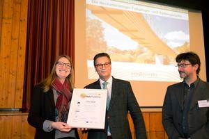 Minister Hauk (Mitte) gratuliert Bürgermeisterin Melanie Gollert zum ProHolzKlima-Publikumspreis, rechts Ortsbaumeister Jürgen Brandt⇥Fotos: Rüdiger Sinn