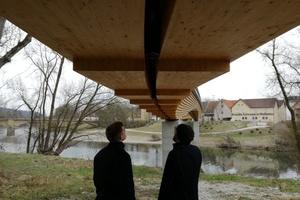 Zwei Teilnehmer betrachten die Neckartenzlinger Brücke aus einer außergewöhnlichen Perspektive