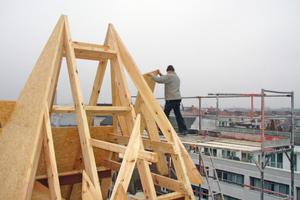 """Der Eckturm des neuen Dachgeschosses wird mit Holzwerkstoffplatten beplankt<span class=""""bildnachweis"""">Foto: Thomas Marsch</span>"""