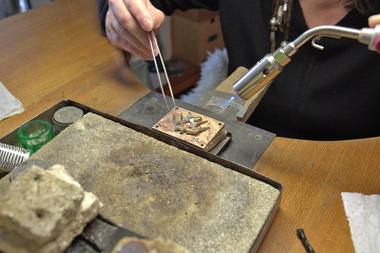 Ein langer Prozess ist es vom Entwurf der Gürtelschnalle bist zum tatsächlichen Produkt: Hier wird ein Zunftzeichen aus Silber auf eine Weltkarte aus Bronze gelötet