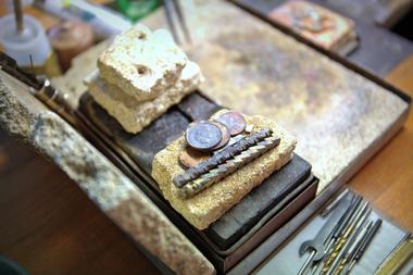 """Münzen und Werkstücke aus der Lehrzeit von Mitra Hadjebi dienen als Unterstützung, etwa zum Aufbocken, beim Löten <span class=""""bildnachweis"""">Fotos: Rüdiger Sinn</span>"""
