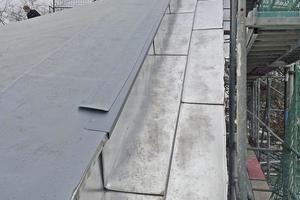 Der mit Blech verkleidete Dachrand im Detail: Ein Anschlussstreifen über Verbundblech und Dachbahnen schützt vor dem Hinterlaufen mit Wasser