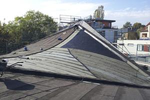 Nach dem Rückbau tragen die Dachdecker einen bituminösen Voranstrich auf. Darüber verkleben sie Elastomerbitumenbahnen als Notabdichtung