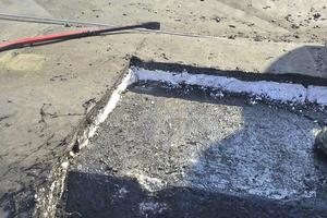 Um Erschütterungen des Betondachs zu vermeiden, arbeiten die Dachdecker beim Rückbau der Abdichtung ohne Maschinen
