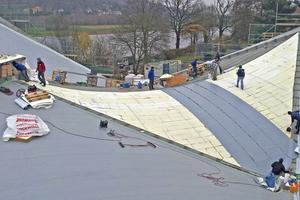 Gedämmt ist das Dach mit verklebten Dämmplatten aus Steinwolle. Darüber verlegen die Dachdecker eine PIB-Kunststoffdachbahn