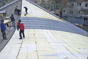 """Für das dünne Betonschalendach kam nur ein verklebter Dachschichtenaufbau in Frage, hier werden die Kunststoffdachbahnen über der Dämmung verlegt<br /> <span class=""""bildnachweis""""></span>"""