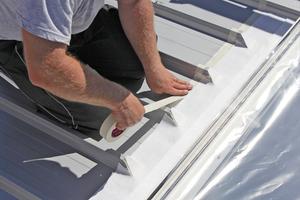 Mit Klebeband wird eine Art Rahmen rund um das Fenster geklebt. Vliesstücke werden passend zur Fenstergröße ausgeschnitten