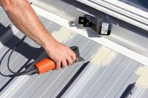 Zum Vorbereiten der Abdichtung wird das Dach um den Aufsetzkranz herum abgeschliffen und gereinigt