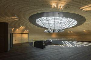 Im zweistöckigen Ausstellungsbereich entfaltet die geschwungene Holzkonstruktion ihre volle Wirkung. Über das Oberlicht im Dach erhält das Atrium natürliches Tageslicht<br />