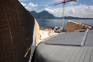 """Rechts: Blick von der Baustelle auf den Lago Maggiore. An der Fassade ist eine braune Schutzfolie über dem Titanzink verlegt, die nach der Bauphase entfernt wird<span class=""""bildnachweis""""> </span>"""