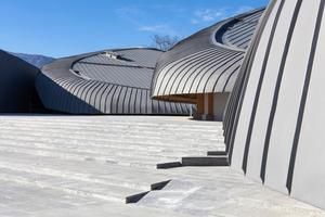 Die gerundeten Gebäude des Kulturzentrums sind mit einer Außenhaut aus vorbewittertem Titanzink verkleidet