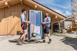 """Mit dem Hebegeschirr """"Karl"""", das als Schultergurt angelegt wird, lassen sich Dachfenster transportieren"""